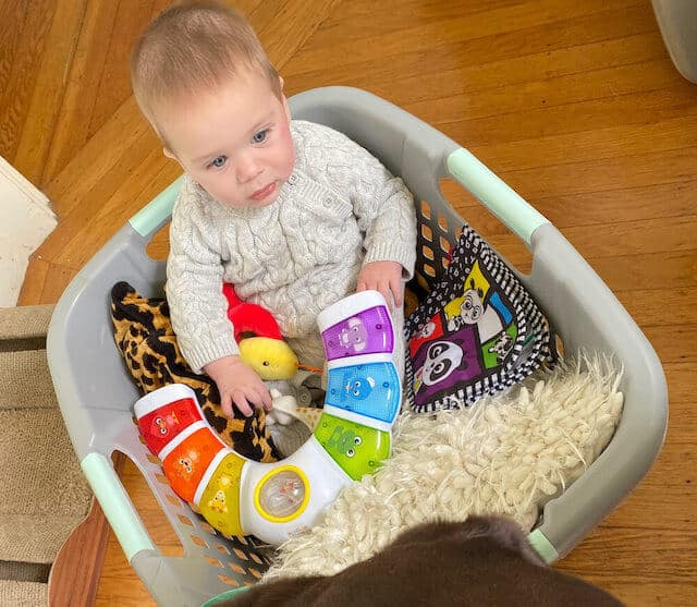 baby playing with toys in laundry basket